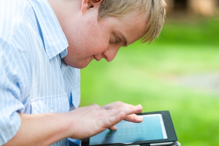 Foto de Close up portrait of handicapped boy outdoors with digital tablet. - Imagen libre de derechos