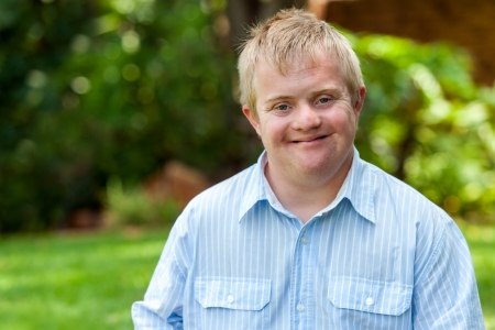 Foto de Portrait of handsome handicapped boy in blue shirt outdoors. - Imagen libre de derechos