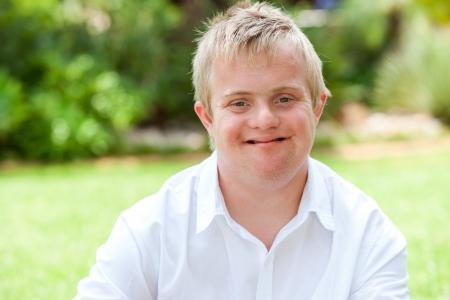 Foto de Close up portrait of boy with down syndrome in white shirt outdoors. - Imagen libre de derechos