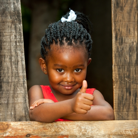 Photo for Portrait of small african girl doing thumbs up at wooden fence. - Royalty Free Image