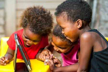 Foto de Close up portrait of three african young girls playing together on digital tablet. - Imagen libre de derechos