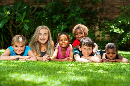 Diversity portrait of children laying together on grass outdoors.