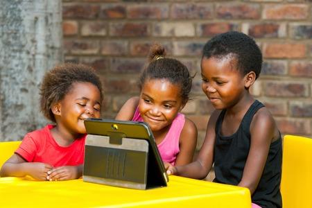 Foto de Portrait of three african girls playing leisure games on tablet. - Imagen libre de derechos