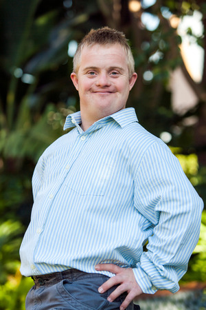 Foto de Portrait of cute boy with down syndrome posing at camera outdoors. - Imagen libre de derechos