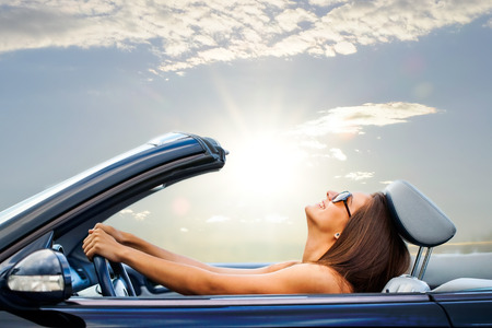 Photo pour Portrait of Young girl driving cabriolet at sunset. - image libre de droit
