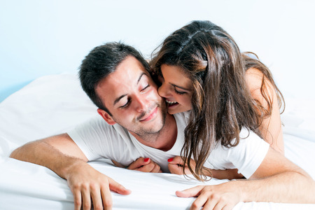 Foto de Portrait of young couple with playful behavior in bedroom. - Imagen libre de derechos