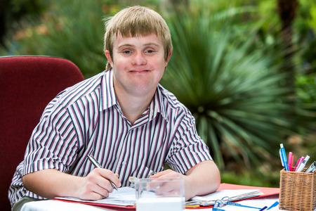Photo pour Close up portrait of young male student with down syndrome at study desk outdoors. - image libre de droit