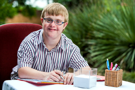 Foto de Close up portrait of handicapped student wearing glasses at desk in garden. - Imagen libre de derechos