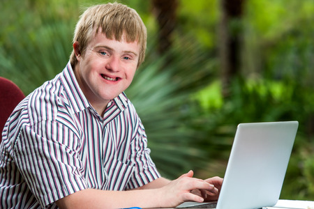 Foto de Portrait of happy handicapped young man typing on laptop in garden. - Imagen libre de derechos