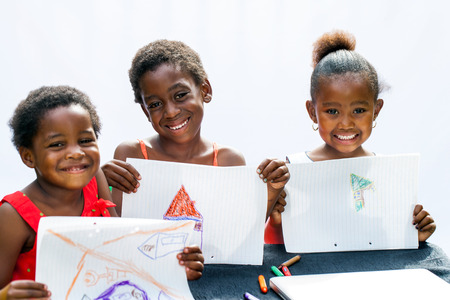 Photo pour Portrait of three African youngsters showing their drawings at desk.Isolated on light background. - image libre de droit