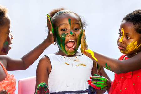 Photo for Portrait of African kids painting themselves with color paint.Isolated against light background. - Royalty Free Image
