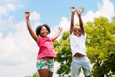 Photo pour Action portrait of young African boy and girl jumping in park. - image libre de droit