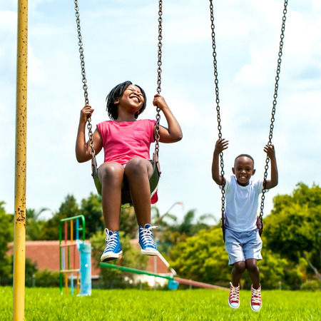 Photo pour Action portrait of African kids having fun swinging in park.Out of focus houses in background. - image libre de droit