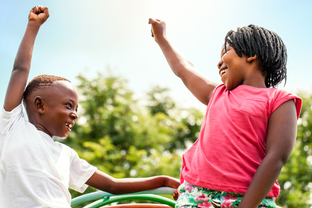 Foto de Close up portrait of two happy African kids looking at each other raising hands outdoors. - Imagen libre de derechos