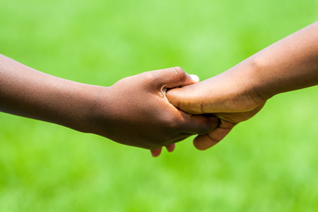 Photo for Extreme close up detail of African kids holding hands against green outdoor background. - Royalty Free Image