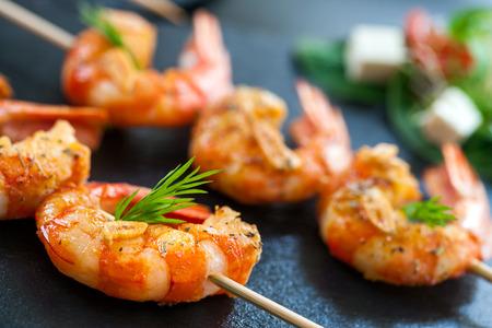 Photo pour Extreme close up detail of appetizing queen prawn brochette. - image libre de droit