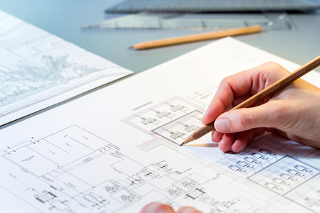Foto de Macro close up of quantity surveyors hand reviewing technical drawing. - Imagen libre de derechos