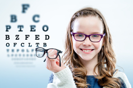 Photo for Close up portrait of young girl holding glasses with test chart in background. - Royalty Free Image
