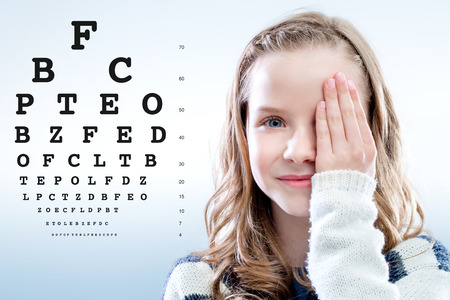 Photo pour Close up portrait of Girl reviewing eye sight closing eye with hand.Test chart in background. - image libre de droit