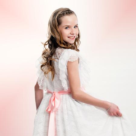 Photo pour Close up studio portrait of cute girl in communion dress. - image libre de droit