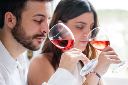 Photo pour Close up portrait of young couple at wine tasting. Man and woman smelling wine with eyes closed. - image libre de droit