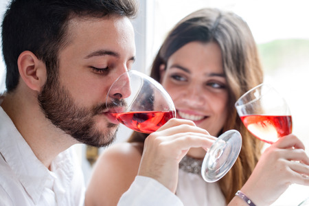 Foto de Close up portrait of Couple enjoying and drinking wine at tasting. - Imagen libre de derechos