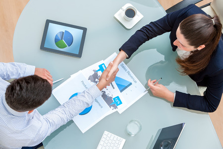 Photo for Top view of young business partners shaking hands on deal at desk in office.Documents and digital tablet on table showing statistics and graphics. - Royalty Free Image