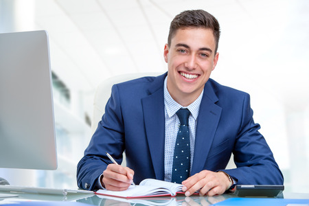 Foto de Close up portrait of young attractive businessman in blue suit at desk in office. Young man writing in agenda with pen. - Imagen libre de derechos
