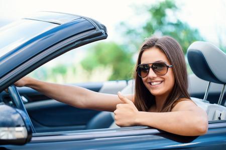Photo pour Close up portrait of Cute girl driving convertible doing thumbs up. - image libre de droit
