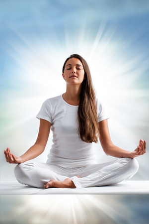 Photo for Close up portrait of attractive young woman meditating with eyes closed. Front view of woman dressed in white in yoga position with ray of light in background. - Royalty Free Image