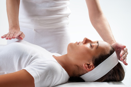 Photo pour Close up of chiropractor's hands doing reiki on young woman.One hand on head and one hand on chest. - image libre de droit