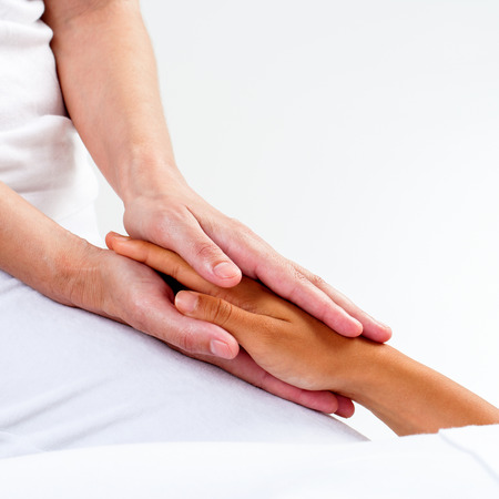 Foto de Macro close up of therapist hands holding woman's hand.Healing treatment at reiki session. - Imagen libre de derechos