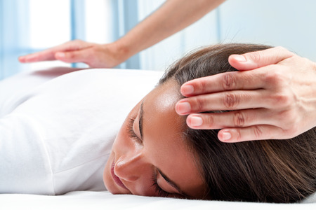 Foto de Therapists hands doing reiki therapy on girl. One hand on head and one hand on back. - Imagen libre de derechos