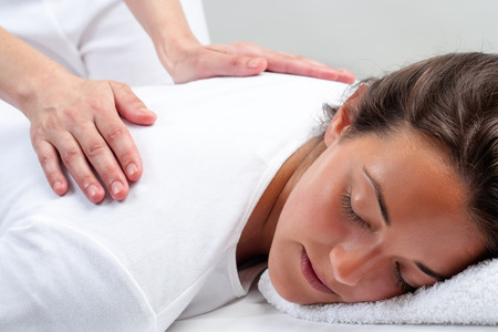 Foto de Close up portrait of young woman laying facing head down.Therapist doing reiki treatment with hands on back. - Imagen libre de derechos