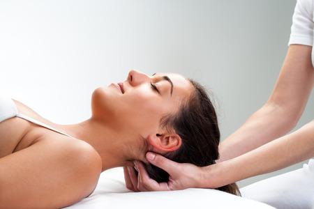 Foto de Close up of  chiropractor pressing back of womans head. Therapist doing healing massage with fingers at back of neck. - Imagen libre de derechos