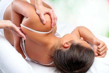 Foto de Close up top view of osteopath doing healing treatment on female shoulder blade. - Imagen libre de derechos