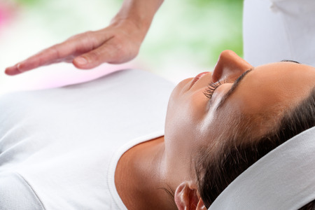 Photo pour Close up portrait of young woman relaxing at reiki session with therapist hand in background. - image libre de droit
