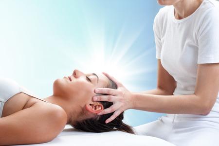Foto de Close up portrait of therapist doing healing treatment on young woman.Therapist touching head with light glow in background. - Imagen libre de derechos
