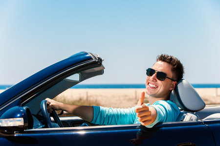 Photo pour Portrait of attractive young man sitting in blue convertible doing thumbs up. - image libre de droit
