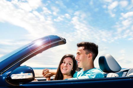 Photo pour Close up portrait of Happy young couple driving blue convertible along seaside. - image libre de droit