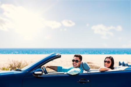 Photo pour Close up portrait of cute teen couple driving blue cabriolet along seaside. - image libre de droit