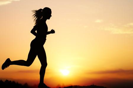 Photo pour Close up action Silhouette of female jogger at sunset.Girl backlit against intense orange sky. - image libre de droit