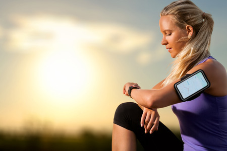 Foto de Portrait of young athlete checking workout on smart watch at sunset.Woman wearing armband with smart watch and graphic showing workout results. - Imagen libre de derechos