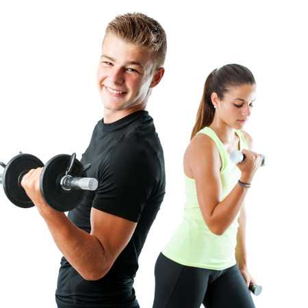 Foto de Close up portrait of handsome teen boy working out with weights.Out of focus girl working out in background.Isolated on white. - Imagen libre de derechos