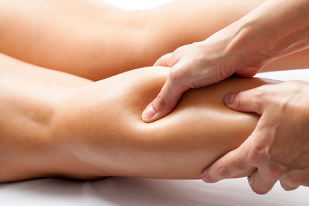 Foto de Extreme close up of osteopath applying pressure with thumb on female calf muscle. - Imagen libre de derechos