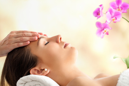 Photo pour Close up  portrait of young Female Facial massage in spa. Therapist massaging woman's head against bright colorful background. - image libre de droit