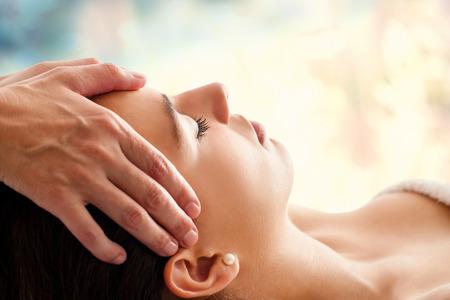 Foto de Close up head portrait of young woman having facial massage in spa. Therapist massaging woman's head against colorful background. - Imagen libre de derechos