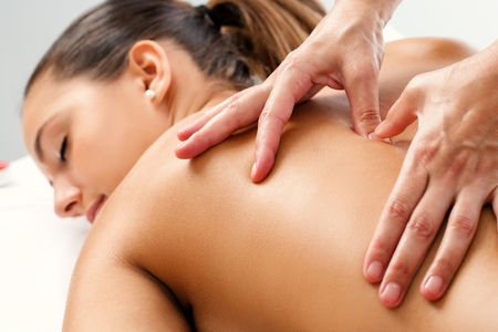 Close up of Therapist doing curative healing massage with thumbs on female back.