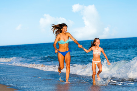Photo for Action portrait of two young happy women running and slashing water  along beach. - Royalty Free Image
