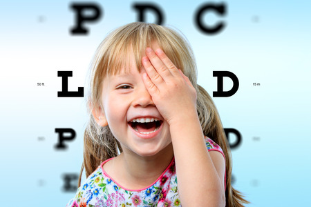 Photo pour Close up face portrait of happy girl having fun at vision test.Conceptual image with girl closing one eye with hand and block letter eye chart in background. - image libre de droit